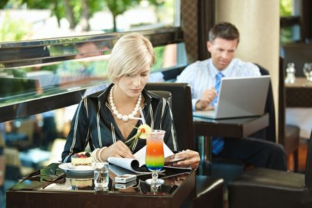 Young woman sitting at table in cafe, reading magazine. Businessman using laptop in the background. photo