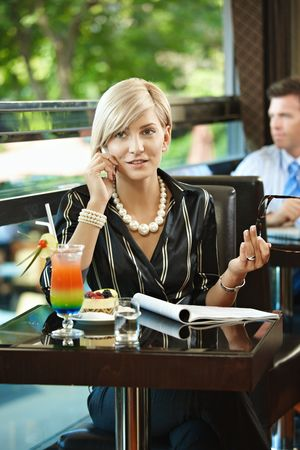 Young businesswoman sitting at table in cafe, talking on mobile phone, reading magazine. photo