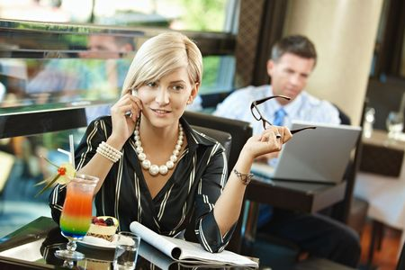 businessman waiting call: Young businesswoman sitting at table in cafe, talking on mobile phone, reading magazine.