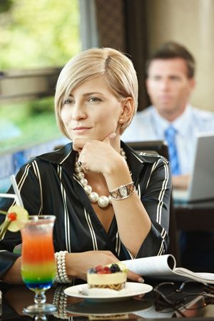 Young woman sitting at table in cafe, reading magazine while waiting for somebody. photo