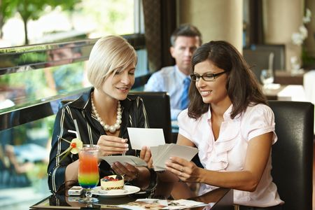 Young women sitting in cafe having sweets, showing photos, smiling. photo