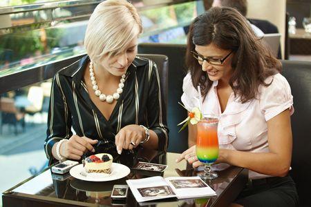 sonograma: Mujer joven feliz sentado en el caf� con dulces, mirando sonograma, sonriendo. Foto de archivo