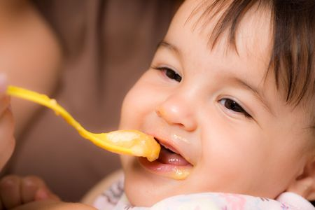 to feed: Mother feeding baby girl with spoon. Stock Photo