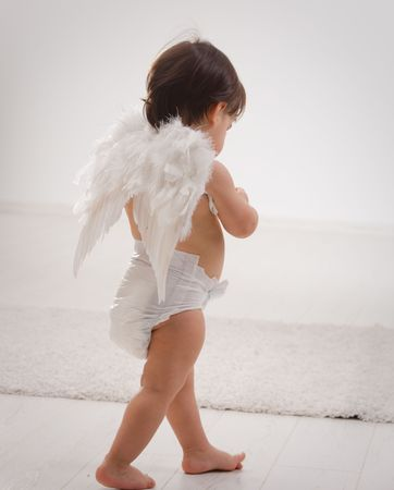 christmas costume: One year old baby girl wearing white angel wings. Back view. Isolated on white background. Stock Photo