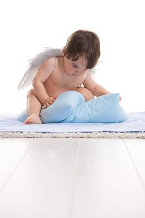 cuddly baby: Baby girl wearing white angel wings, playing with blue pillows. Isolated on white background.