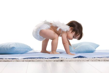 Baby girl wearing white angel wings, playing with blue pillows. Isolated on white background. photo