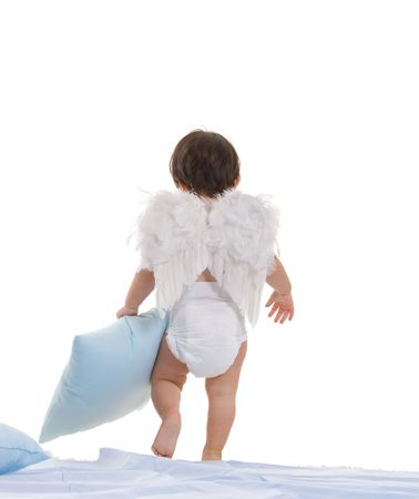Baby girl wearing white angel wings, carying blue pillows, going to sleep. Back view, isolated on white background. photo