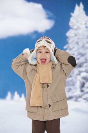 three persons only: Portrait of happy kid wearing warm clothes in snow on a cold winter day, smiling. Stock Photo
