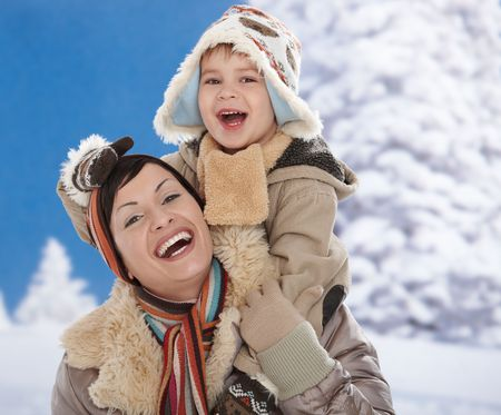 december: Portrait of happy mother and child  together in snow on a cold winter day laughing, smiling. Stock Photo