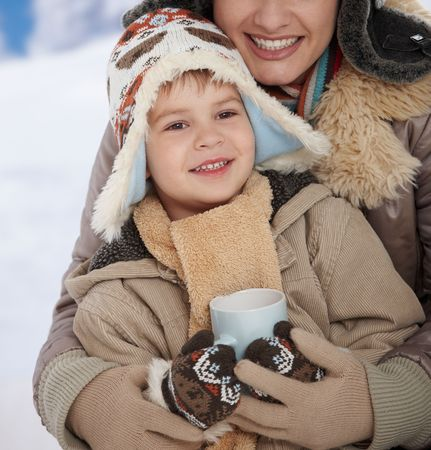 cup four: Portrait of happy mother and child holding cup of hot tea in snow on a cold winter day laughing, smiling.