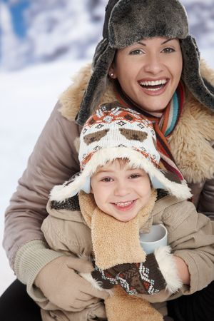 Portrait of happy mother and child holding cup of hot tea in snow on a cold winter day laughing, smiling. photo