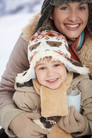 seasonal clothes: Portrait of happy mother and child holding cup of hot tea in snow on a cold winter day laughing, smiling.