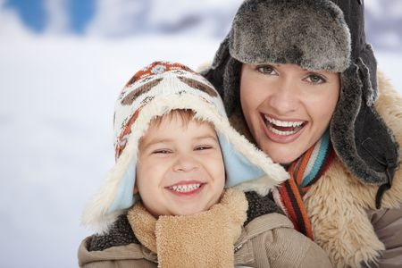 one parent: Portrait of happy mother and child  together in snow on a cold winter day laughing, smiling. Stock Photo
