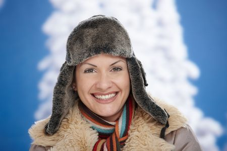 Happy young woman in snow at winter wearing warm clothes, looking at camera, smiling. photo