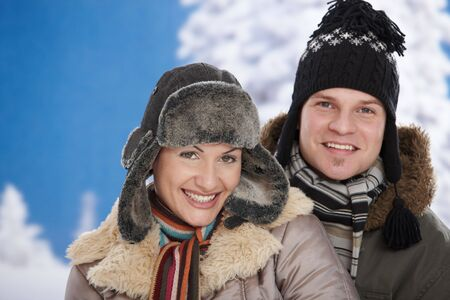 Happy couple in snow at winter wearing warm clothes, looking at camera smiling. Stock Photo - 5806434