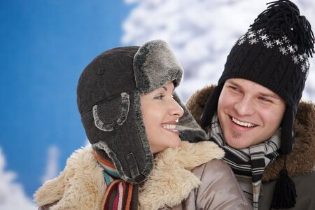 Happy couple in snow at winter wearing warm clothes, smiling. photo