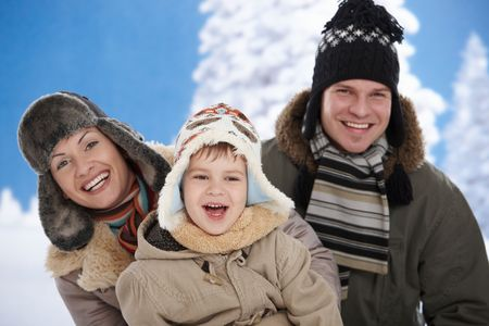 seasonal clothes: Portrait of happy family together outdoor in snow on a cold winter day, laughing, smiling. Stock Photo