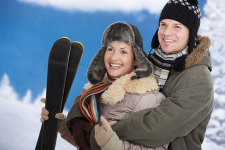 Happy couple in snow at winter wearing warm clothes, smiling. Woman holding skis. Stock Photo - 5806438