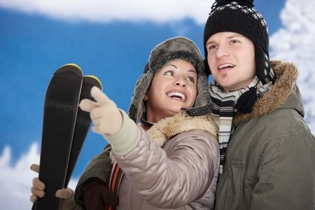 Happy couple in snow at winter wearing warm clothes, smiling. Woman holding skis. photo