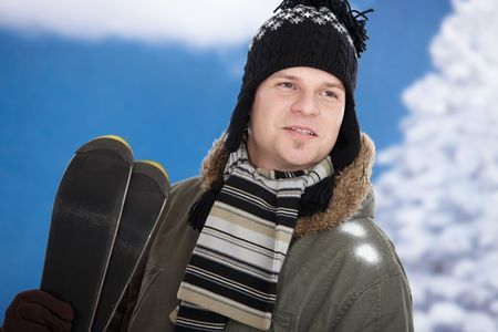 Smiling young man in snow at winter holding skis, photo