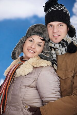 Happy couple in snow at winter wearing warm clothes, looking at camera smiling. Stock Photo - 5806435