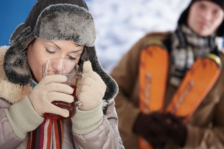 Young couple in snow at winter wearing warm clothes, smiling. Woman drinking cup of hot tea. photo
