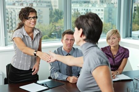 Panel of Business Leute sitzen am Tisch im Sitzungssaal der Durchführung von Bewerbungsgesprächen Gruß weiblichen Bewerber.