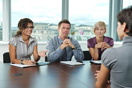 job promotion: Panel of business people sitting at table in meeting room conducting job interview talking with applicant.