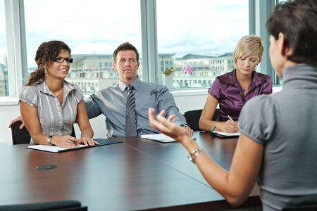 entrevista de trabajo: Grupo de gente de negocios sentado a la mesa en la sala de reuniones realizaci�n de la entrevista de trabajo a hablar con el solicitante.