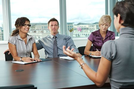 Panel of business people sitting at table in meeting room conducting job interview talking with applicant.  photo