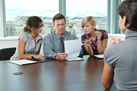 hire: Panel of business people sitting at table in meeting room conducting job interview looking at documents.