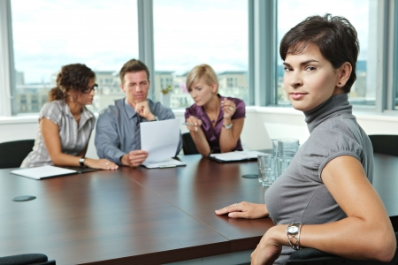 job satisfaction: Panel of business people sitting at table in meeting room conducting job interview. Applicant looking at camera.  Stock Photo