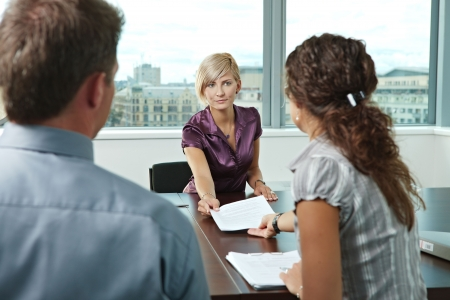 Attractive woman applicantshowing documents during job interview. Over the shoulder view. photo