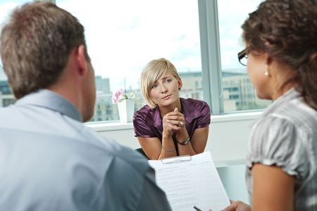 job promotion: Woman applicant craving for job during job interview. Over the shoulder view.