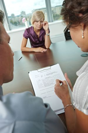 Woman applicant crying during job interview. Over the shoulder view. Focus placed on sheet in front all results are bad. photo