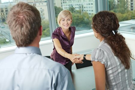 open collar: Business people shaking hands over meeting table at office, smiling.