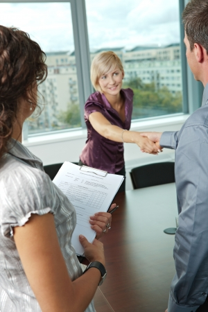 job satisfaction: Successful job interview - happy employee shaking hands, smiling. Focus places on questionnarie in front, reults are excellent.  Stock Photo