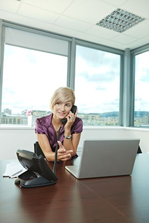 open collar: Happy young businesswoman sitting at table in office meeting room, talking on phone, smiling.