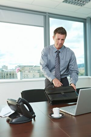 Morning in the office. Businessman arriving to desk, holding suitcase.  photo