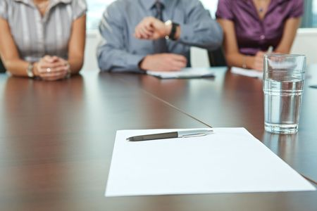 Focus on paper and pen on table. In the background panel of business people sitting conducting job interview.  photo