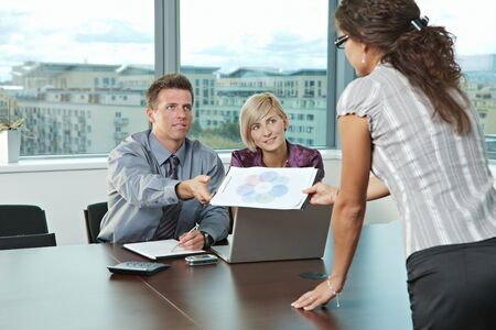 Young business people working in team at office meeting room. Businesswoman showing diagram to parners. photo