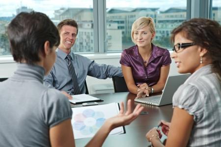 Groep jonge mensen uit het bedrijfsleven praten over zakelijke bijeenkomst op het kantoor.