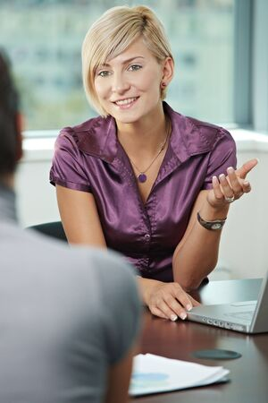gratified: Smiling business people talking on business meeting. Over the shoulder view.