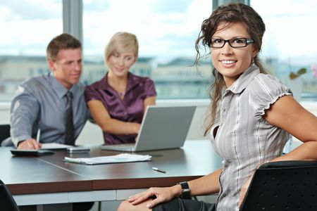 Smiling businesswoman on business meeting at office with team in background. Stock Photo - 5806507
