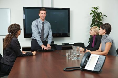 Business people sitting around meeting table in board room. photo