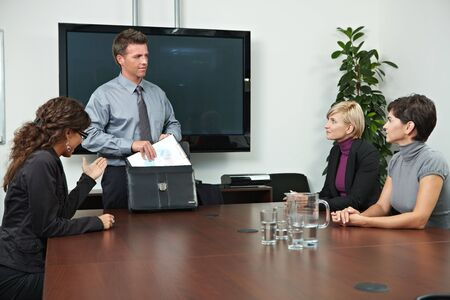 collaborating together: Business people sitting around meeting table in board room. Stock Photo