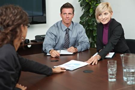 n�gocier: Les gens d'affaires assis autour d'une table de r�union en salle de conseil, de parler.