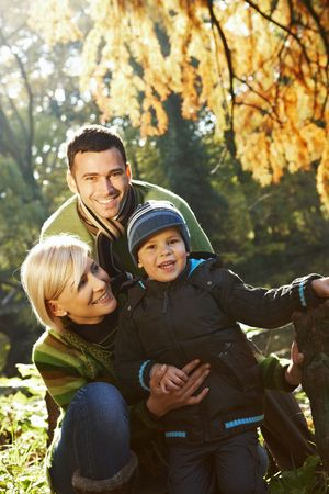 sunligh: Happy family looking at camera, smiling outdoor in park at autumn.