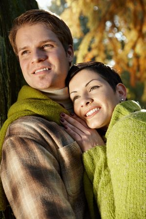 sunligh: Young love couple hugging outdoor in park at autumn, smiling.