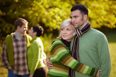 sunligh: Young love couples hugging and walking in park outdoor at autumn, smiling.